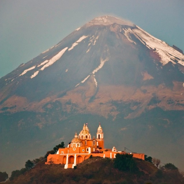 Mansion on the hill. Popocatepetl Volcano in the background. Photo was taken from a highway overpass in Puebla Mexico. 2010.