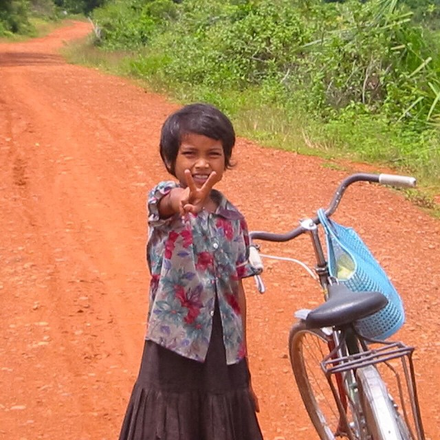 Peace out. Happy Monday. This little girl is actually asking for $2. I was riding my bike around the Ankor Wat temples and came across this girl. August 2002 Cambodia.