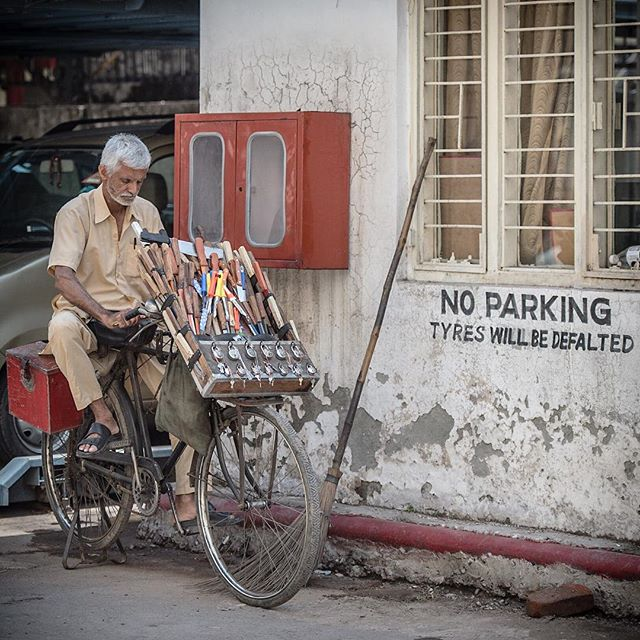 Love this photo. If you look closely on the wall if you park there they will deflate your tires. The guy on the bike is on super deluxe model that sharpens knives and scissors as well as selling locks. Only in India. New Delhi India -April 2015
