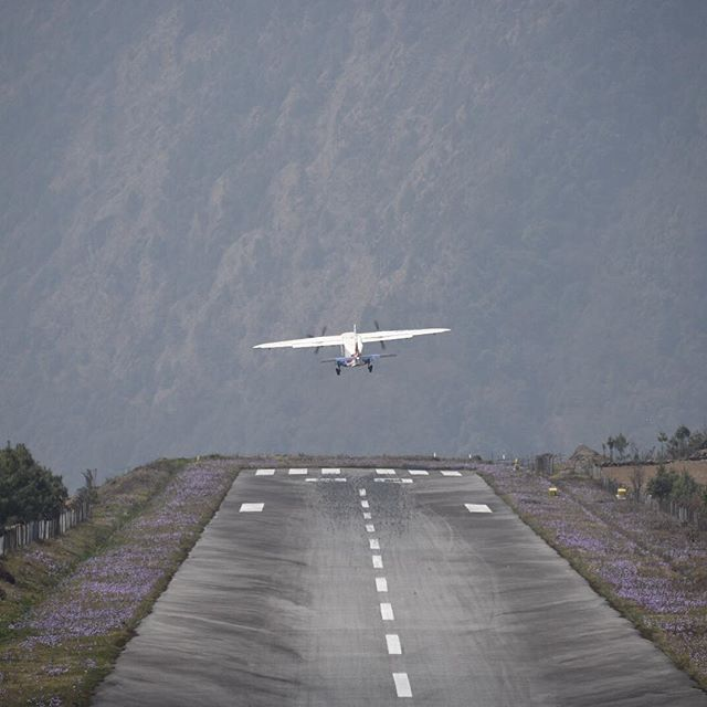 Tenzing Hillary Airport. Lukla, Nepal. The landing here is unreal. The runway slopes up 168 ft and drops off 10000 ft.  Bonus spring wildflowers on the side.